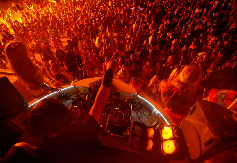 """People dance for a DJ at the Dancetronauts mutant vehicle during the Burning Man 2014 """"Caravansary"""" arts and music festival in the Black Rock Desert of Nevada"""