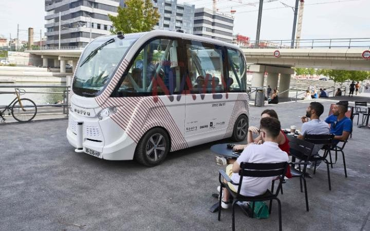 107449818_People_sit_in_a_cafe_as_passengers_ride_in_a_new_electric_and_autonymous_bus_operatingWORLD-large_trans++_MBhvjUqhIfRd2_dxg_gJ_gjUujgyGHD9_13S00ocvk