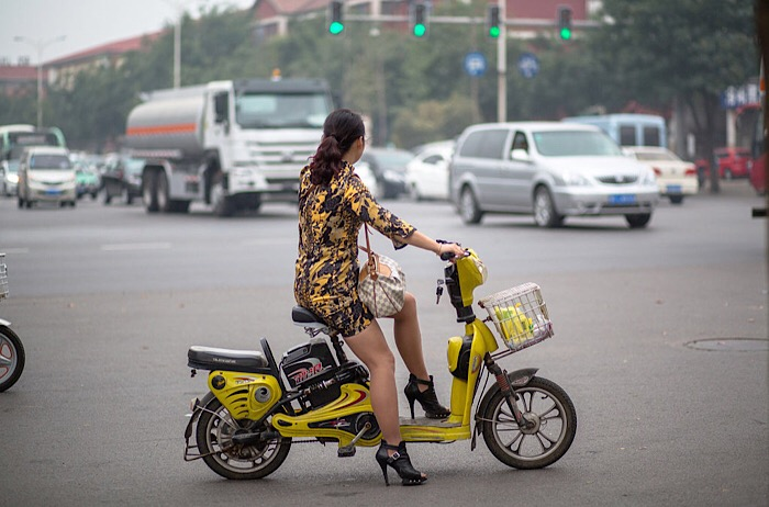 A fashionable girl sits on her e-bike.  China now has an in