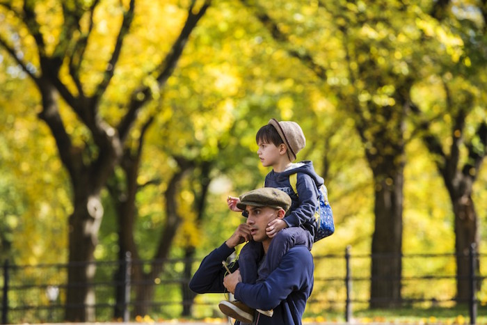 A man carries a young boy on his shoulders while walking inside Central Park as the colors of autumn become more prevalent in New York