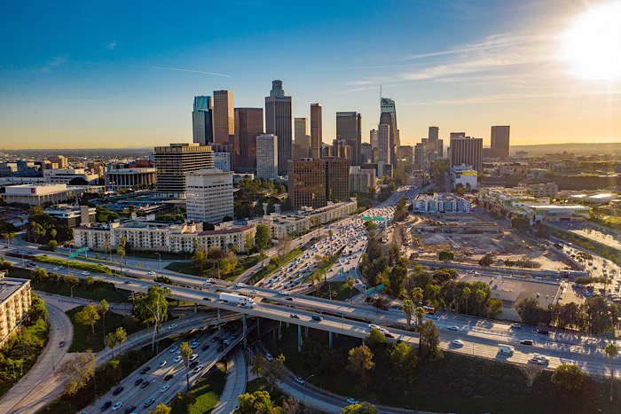 Drone view of downtown Los Angeles or LA skyline with skyscrapers and freeway traffic below.